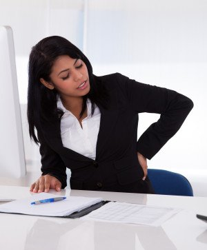 girl in cubicle with back pain