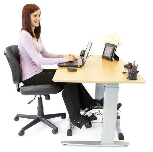 girl using desk exercise bike in cubicle