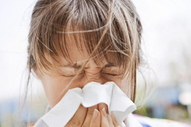girl with allergies blowing nose