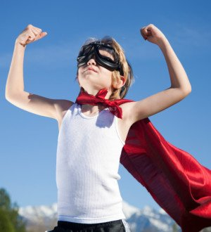 little boy with superman cape flexing muscles