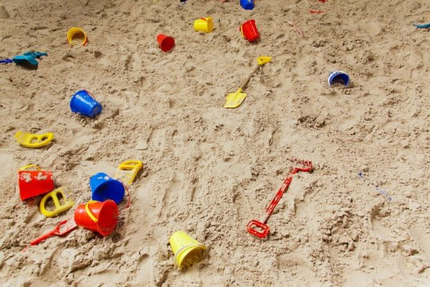 beach scene with colorful childrens pale and shovel toys
