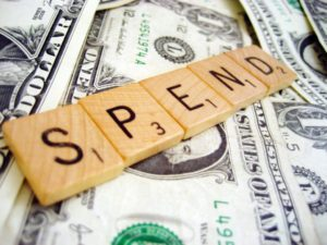 "scrabble pieces spelling ""SPENDING"" over dollar bill background"